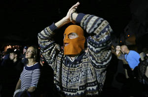 Photo -   A masked spectator reacts during the concert organized to support jailed Pussy Riot musicians in St.Petersburg, Russia, Sunday, Sept. 9, 2012. A Moscow judge has sentenced each of three members of the provocative punk band Pussy Riot to two years in prison on hooliganism charges following a trial that has drawn international outrage as an emblem of Russia's intolerance to dissent. (AP Photo/Dmitry Lovetsky)