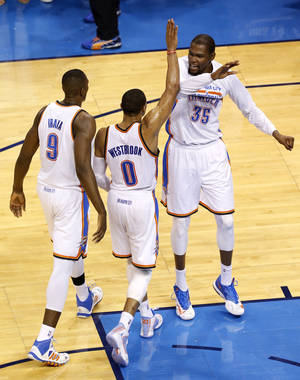Photo - Oklahoma City's Russell Westbrook (0) celebrates his half court shot with Serge Ibaka (9) and Kevin Durant (35) during Game 3 of the Western Conference Finals in the NBA playoffs between the Oklahoma City Thunder and the San Antonio Spurs at Chesapeake Energy Arena in Oklahoma City, Sunday, May 25, 2014. Photo by Nate Billings, The Oklahoman