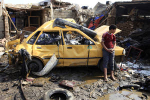 Photo - An Iraqi boy stands near a destroyed car at the scene of a car bomb attack in Baghdad's northern Kazimyah neighborhood, Friday, Feb. 8, 2013. Car bombs struck two outdoor markets in Shiite areas of Iraq on Friday, killing and wounding scores of people, police said. (AP Photo/ Karim Kadim)