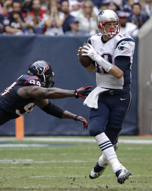 Photo - New England Patriots' Tom Brady, right, looks to pass as he is pressured by Houston Texans' Antonio Smith (94) during the third quarter of an NFL football game on Sunday, Dec. 1, 2013, in Houston. (AP Photo/David J. Phillip)