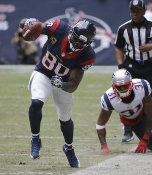 Photo - Houston Texans' Andre Johnson (80) works to stay inbounds after making a catch as New England Patriots' Aqib Talib (31) looks on during the third quarter of an NFL football game Sunday, Dec. 1, 2013, in Houston. (AP Photo/David J. Phillip)