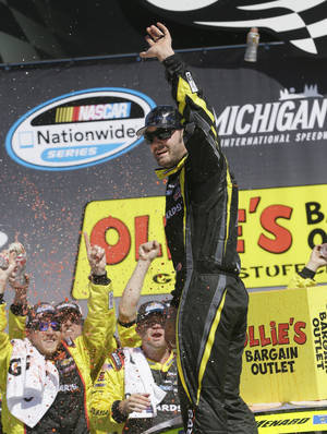 Photo - Driver Paul Menard acknowledges the crowd as he celebrates in Victory Lane after winning the NASCAR Nationwide series  auto race at Michigan International Speedway in Brooklyn, Mich., Saturday, June 14, 2014. (AP Photo/Carlos Osorio)
