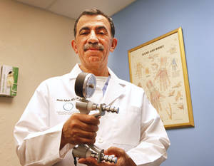 Photo - Dr. Mehdi Adham holds a device used to test a person's strength and better determine whether they suffer from carpal tunnel syndrome. Adham regularly performs carpal tunnel surgeries in the Oklahoma City area. Photo by David McDaniel, The Oklahoman