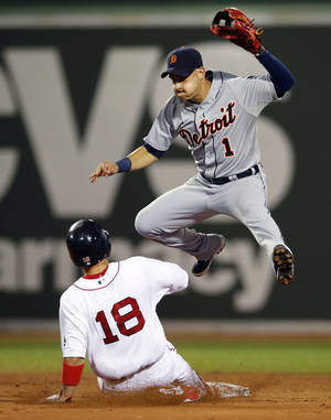 Photo - Detroit Tigers shortstop Jose Iglesias (1) jumps to avoid a sliding Boston Red Sox's Shane Victorino (18) as he turns a double play on Dustin Pedroia at first during the third inning of a baseball game at Fenway Park in Boston, Wednesday, Sept. 4, 2013. (AP Photo/Elise Amendola)