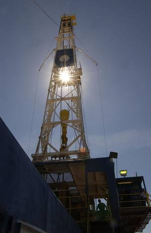 photo -   FILE - An oil rig worker is silhouetted against the huge Nabors oil rig near Sidney, Mont., in Richland County, in this Sept., 2004 file photo, as he walks down the stairway. Sidney isn't the first small town in the West to get run over by a gold rush, in this case black gold — more than 16 million barrels of crude being pumped every month from the massive Bakken oil field beneath eastern Montana and western North Dakota. (AP Photo/Billings Gazette, David Grubbs)
