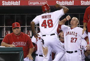 Photo -   Los Angeles Angels' Torii Hunter, center, is greeted by teammate Mike Trout, right, after Hunter scored on a single by Howard Kendrick in the fourth inning of a baseball game against the Texas Rangers in Anaheim, Calif., Tuesday, Sept. 18, 2012. Los Angeles Angels manager Mike Scioscia, left, sits in the dugout. (AP Photo/Jae C. Hong)
