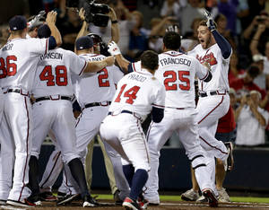 photo -   Atlanta Braves' Freddie Freeman, right, celebrates with teammates after hitting a two-run home run in the ninth inning to beat the Miami Marlins 4-3 in a baseball game Tuesday, Sept. 25, 2012, in Atlanta. The Braves clinched at least an NL wild-card berth. (AP Photo/David Goldman)