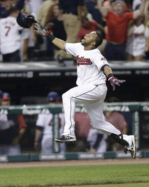 Photo - Cleveland Indians' Carlos Santana celebrates after rounding third base on his solo home run off Chicago White Sox relief pitcher Dylan Axelrod in the 10th inning of a baseball game, Wednesday, July 31, 2013, in Cleveland. The Indians won 6-5 in 10 innings. (AP Photo/Tony Dejak)