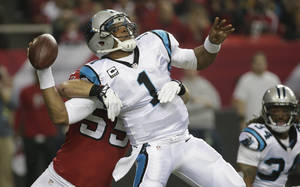 Photo - Carolina Panthers quarterback Cam Newton (1) is hit by Atlanta Falcons outside linebacker Paul Worrilow (55) during the first half of an NFL football game, Sunday, Dec. 29, 2013, in Atlanta. The play was ruled as a incomplete pass. (AP Photo/Dave Martin)