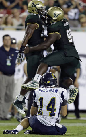 Photo -   Chattanooga quarterback Jacob Huesman (14) watches South Florida linebacker Sam Barrington (36) and Todd Chandler (95) celebrate a sack during the third quarter of an NCAA college football game Saturday, Sept. 1, 2012, in Tampa, Fla. (AP Photo/Chris O'Meara)