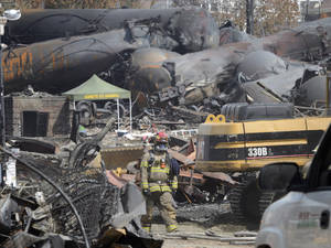 Photo - FILE - This July 6, 2013 file photo shows a worker, wearing protective gear moving though the wreckage of the oil train derailment and explosion in  in Lac-Megantic, Quebec. Responding to a series of fiery train derailments, federal regulators said Wednesday they will propose that trains transporting crude oil have at least two-man crews and requirements aimed at preventing parked train cars from coming loose and causing an accident like one in July that killed 47 people. The Federal Railroad Administration had asked a freight rail industry advisory committee to make recommendations on whether two-man crews should be required, but the industry officials were unable to reach a consensus after working on the issue for months. Federal officials said they decided to move ahead with the two-crew member requirement anyway.  (AP Photo/Ryan Remiorz, File, Pool)