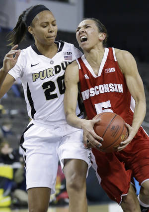 photo - Wisconsin guard Morgan Paige, right, drives to the basket against Purdue guard Dee Dee Williams during the first half of an NCAA college basketball game in the Big Ten Conference tournament in Hoffman Estates, Ill., on Friday, March 8, 2013. (AP Photo/Nam Y. Huh)