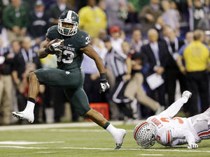 Photo - Michigan State's Jeremy Langford (33) runs out of the tackle of Ohio State's Corey Brown (3) for a 26-yard touchdown run during the fourth quarter of an Big Ten Conference championship NCAA college football game Saturday, Dec. 7, 2013, in Indianapolis. (AP Photo/Michael Conroy)