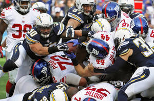 Photo - New York Giants running back Peyton Hillis carries the ball into the end zone while San Diego Chargers linebacker Manti Te'o attempts to take the ball away on a 1-yard touchdown run during the second half of an NFL football game on Sunday, Dec. 8, 2013, in San Diego. (AP Photo/Denis Poroy)