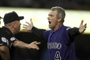 photo -   Colorado Rockies manager Jim Tracy argues with umpire Mike Everitt (57) over a controversial call on a play in center field off Los Angeles Dodgers hitter Shane Victorino in the seventh inning of a baseball game at Dodger Stadium in Los Angeles Monday, Aug. 8, 2012. The ball was ruled fair and Victorino took first base.(AP Photo/Reed Saxon)  