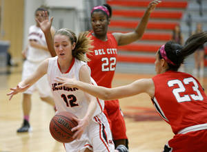 Photo - Westmoore's Sydney Chastain drives past  Del City's Ossyana Ozoani, center, and Breail Goodlow during their girls basketball game at Westmoore High School in Moore, Okla., Friday, Feb. 14, 2014. Photo by Bryan Terry, The Oklahoman