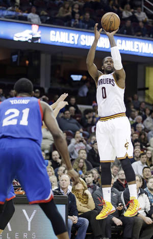Photo - Cleveland Cavaliers' C.J. Miles (0) shoots a three-pointer against the Philadelphia 76ers during the first quarter of an NBA basketball game Tuesday, Jan. 7, 2014, in Cleveland. (AP Photo/Tony Dejak)