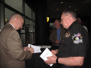"Photo - Steve Scheibner, keynote speaker at the 29th annual Metro Prayer Breakfast, signs a copy of the book ""In My Seat"" for Oklahoma County Sheriff John Whetsel after the breakfast Wednesday at the Cox Convention Center in downtown Oklahoma City. The book was written by Scheibner's wife Megan and chronicles his life in the aftermath of Sept. 11, 2001 terrorist attacks. <strong>CARLA HINTON - CARLA HINTON</strong>"