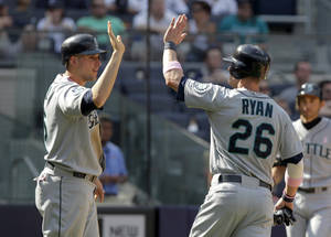 Photo -   Seattle Mariners' Brendan Ryan, right, and Alex Liddi celebrate after scoring on a single by Casper Wells during the ninth inning of a baseball game against the New York Yankees at Yankee Stadium in New York, Sunday, May 13, 2012. The Mariners defeated the Yankees 6-2. (AP Photo/Seth Wenig)