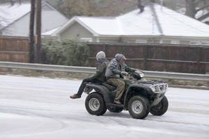 Photo - Two people ride a all terrain vehicle on a sleet-covered street in Little Rock, Ark., Friday, Dec. 6, 2013. Weather forecasters lifted an ice storm warning Friday for much of central Arkansas. (AP Photo/Danny Johnston)
