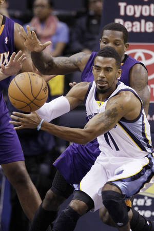 Photo - Memphis Grizzlies' Mike Conley (11) passes the ball in front of Phoenix Suns' Eric Bledsoe in the first half of an NBA basketball game in Memphis, Tenn., Tuesday, Dec. 3, 2013. (AP Photo/Danny Johnston)