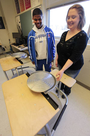 Photo - On Thursday, John Marshall High School senior Carltrel Parker and visual arts teacher Kyla Kaufman look over pottery equipment donated by the Midtown  Rotary. Photo By David McDaniel, The Oklahoman