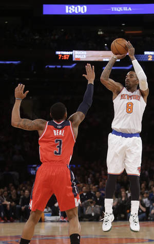 Photo - New York Knicks' J.R. Smith (8) shoots over Washington Wizards' John Wall (2) during the first half of an NBA basketball game Friday, April 4, 2014, in New York. (AP Photo/Frank Franklin II)