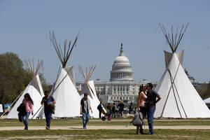 Photo - FILE - In this April 21, 2014, file photo, people walk near teepees set up on the National Mall in Washington, looking toward the Capitol. Days after President Barack Obama touted executive actions aimed at increasing energy efficiency, a bill with similar goals is expected to fall victim to partisan gridlock in the Senate. A bipartisan bill to promote many of the same efficiency goals Obama touted May 9 in California is expected to go down in defeat May 12 amid a dispute over the Keystone XL oil pipeline. (AP Photo/Alex Brandon, File)