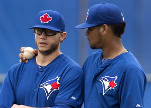 Photo - Toronto Blue Jays Brett Cecil, left, and Esmil Rogers talk during spring training baseball practice Saturday, Feb. 22, 2014 in Dunedin, Fla. (AP Photo/The Canadian Press, Frank Gunn)