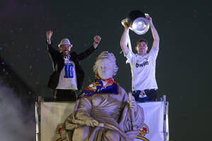 Photo - Real Madrid's goalkeeper Iker Casillas, right, lifts the trophy with Sergio Ramos next to the Cibeles statue in Madrid, Spain, Sunday, May 25, 2014, after their team won the Champions League final soccer match in Lisbon, Portugal by beating Atletico Madrid. (AP Photo/Paul White)