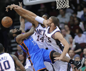 Photo - Nets center Brook Lopez, right, and forward Derrick Favors blocks a shot by Thunder guard James Harden. AP PHOTO