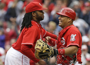 Photo - Cincinnati Reds catcher Brayan Pena, right, congratulates starting pitcher Johnny Cueto after the Reds defeated the San Diego Padres 5-0 in a baseball game, Thursday, May 15, 2014, in Cincinnati. Cueto pitched a complete game, three-hit, shutout.  (AP Photo/Al Behrman)