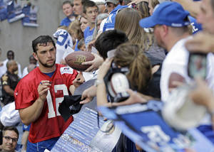 Photo -   Indianapolis Colts' Andrew Luck (12) signs autographs for fans following a NFL football practice on Wednesday, June 13, 2012, in Indianapolis (AP Photo/Darron Cummings)