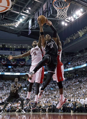 Photo - Brooklyn Nets forward Paul Pierce (34) drives to the basket against Toronto Raptors forward Amir Johnson (15) during the second half of Game 2 in an NBA basketball first-round playoff series, Tuesday, April 22, 2014, in Toronto. Toronto won 100-95. (AP Photo/The Canadian Press, Frank Gunn)
