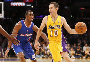 Photo - Los Angeles Lakers' Steve Nash, right, passes off the ball as Los Angeles Clippers' Chris Pauldefends during the first half of an NBA basketball game in Los Angeles, Tuesday, Oct. 29, 2013. (AP Photo/Danny Moloshok)