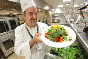 Photo - Chef Steve Delidow, 48, holds a greenhouse salad made with organic cucumber, purple cherry tomatoes, orange cherry tomatoes, rouge d'hiver red romaine lettuce and red lead lettuce, basil, microgreens and nasturtiums in the main kitchen at Henry Ford West Bloomfield Hospital in West Bloomfield, Michigan on September 4, 2012. The organic vegetables were grown in the hospital's greenhouse. (Patricia Beck/Detroit Free Press/MCT)
