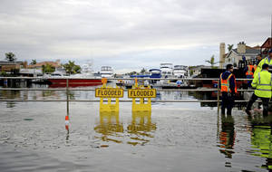 Photo - Officials stand near a flooded marina Wednesday morning, Dec. 13, 2012 in the Sunset Beach area of Huntington Beach, Calif. Astronomical high tides have caused minor street flooding in some low-lying areas along the Southern California coast. (AP Photo/The Daily Breeze, Sean Hiller)  MAGS OUT; NO SALES