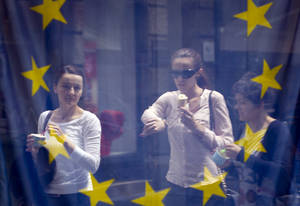Photo - A street scene is reflected in the window of a library with an EU flag on display  in downtown  Zagreb, Croatia, Sunday, June 30, 2013. Croatia is to join the European Union on July 1, 2013. (AP Photo/Darko Bandic)