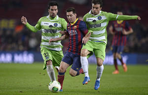 Photo - FC Barcelona's Lionel Messi, from Argentina, center, duels for the ball against Getafe¥s Pedro Leon, right, and Juan Rodriguez, left, during a Copa del Rey soccer match at the Camp Nou stadium in Barcelona, Spain, Wednesday, Jan. 8, 2014. (AP Photo/Manu Fernandez)