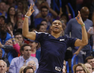 Photo - Oklahoma City Thunder guard Russell Westbrook celebrates a Thunder basket from the bench in the first quarter of an NBA basketball game against the Denver Nuggets in Oklahoma City, Monday, March 24, 2014. (AP Photo/Sue Ogrocki)