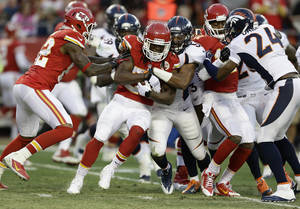 Photo - Kansas City Chiefs running back Jamaal Charles (25) tries to avoid a tackle by Denver Broncos middle linebacker Wesley Woodyard (52) during the first half of an NFL football game, Sunday, Dec. 1, 2013, in Kansas City, Mo. (AP Photo/Charlie Riedel)