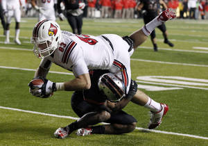 Photo - A Rutgers defender tackles Louisville tight end Ryan Hubbell during the first half of an NCAA college football game in Piscataway, N.J., Thursday, Nov. 29, 2012. (AP Photo/Mel Evans)