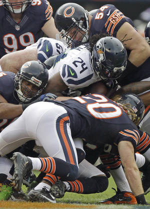 Photo - Seattle Seahawks running back Marshawn Lynch (24) is tackled by Chicago Bears safety Craig Steltz (20) and linebacker Brian Urlacher (54) in the first half of an NFL football game in Chicago, Sunday, Dec. 2, 2012. (AP Photo/Kiichiro Sato)