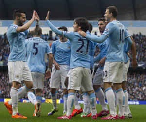 Photo - Manchester City's Edin Dzeko, right, celebrates with teammates after scoring against Cardiff City during their English Premier League soccer match at the Etihad Stadium, Manchester, England, Saturday Jan 18, 2014. (AP Photo/Jon Super)
