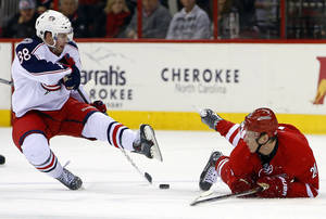 Photo - Carolina Hurricanes' Alexander Semin (28) of Russia, lies on the ice after colliding with Columbus Blue Jackets' Boone Jenner (38) during the first period of an NHL hockey game in Raleigh, N.C., Monday, Dec. 23, 2013. (AP Photo/Karl B DeBlaker)