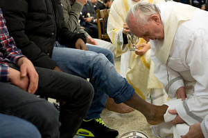 Photo - In this photo provided by the Vatican newspaper L'Osservatore Romano, Pope Francis washes the foot of an inmate at the juvenile detention center of Casal del Marmo, Rome, Thursday, March 28, 2013. Francis washed the feet of a dozen inmates at a juvenile detention center in a Holy Thursday ritual that he celebrated for years as archbishop and is continuing now that he is pope. Two of the 12 were young women, an unusual choice given that the rite re-enacts Jesus' washing of the feet of his male disciples. The Mass was held in the Casal del Marmo facility in Rome, where 46 young men and women currently are detained. Many of them are Gypsies or North African migrants, and the Vatican said the 12 selected for the rite weren't necessarily Catholic. (AP Photo/L'Osservatore Romano, ho)