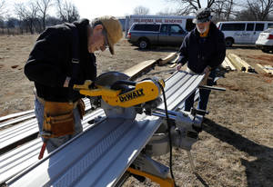 Photo - Dick Greenwood, 79, and Bob Blosser, 69, members of the Nail Benders group, cut skirting for a mobile home in LIttle Axe.  <strong>STEVE SISNEY - THE OKLAHOMAN</strong>