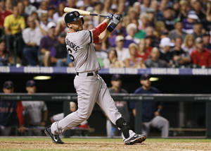 Photo - Boston Red Sox's Will Middlebrooks follows the flight of his three-run home run against the Colorado Rockies in the fifth inning of the Red Sox's 15-5 victory in a baseball game in Denver on Wednesday, Sept. 25, 2013. (AP Photo/David Zalubowski)