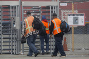 photo - Port workers return to work at the Port of Long Beach Wednesday, Dec. 5,  2012. Work resumed at the Los Angeles and Long Beach harbors after settlement of a strike that crippled the nation's busiest container port complex for more than a week. (AP Photo/Nick Ut)