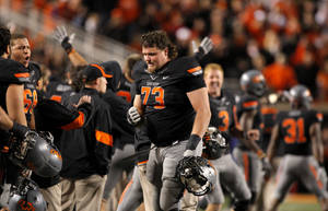 Photo - Oklahoma State's Levy Adcock (73) celebrates a defensive stop late in the fourth quarter during a college football game between the Oklahoma State University Cowboys (OSU) and the Kansas State University Wildcats (KSU) at Boone Pickens Stadium in Stillwater, Okla., Saturday, Nov. 5, 2011.  Photo by Sarah Phipps, The Oklahoman
